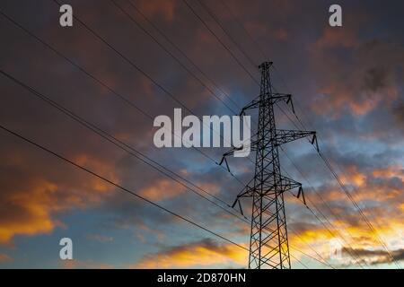 Transmission power tower on background of dramatic colorful sky. Lattice tower, used to support an overhead power line. - Stock Photo
