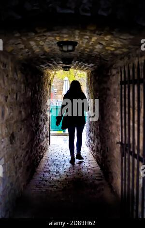 Silhouette of woman person tourist walking in Quebec City, Canada near Lower old town with cobblestone street narrow alley Passage De La Batterie with - Stock Photo