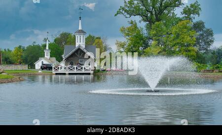 Old Restored White Barns with Cupolas and 5 Pointed Stars by a Pond with a Fountain