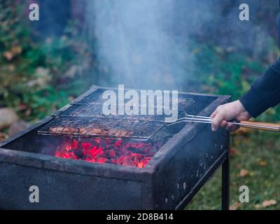 Barbecue grill over the barbecue in the hands of a man. Juicy and fresh pieces of pork are fried over charcoal. Fragrant smoke and hot charcoal - Stock Photo