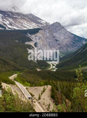 Columbia Icefields Parkway in Jasper National Park, Alberta, Canada.  Rugged Rocky Mountains, highway winding through valley bottom in the distance.