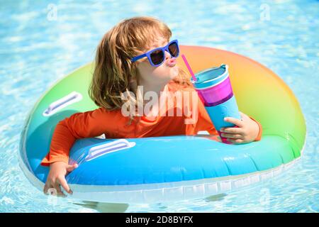 Summer child cocktail party in watter pool in the summer. Little boy relax and swimming in swimming pool with flotation ring on summer. Water toys and - Stock Photo