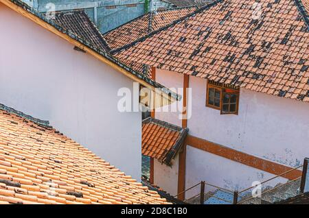 Old houses with orange tiled roofs, narrow streets. View from above. Asia, Bali. - Stock Photo