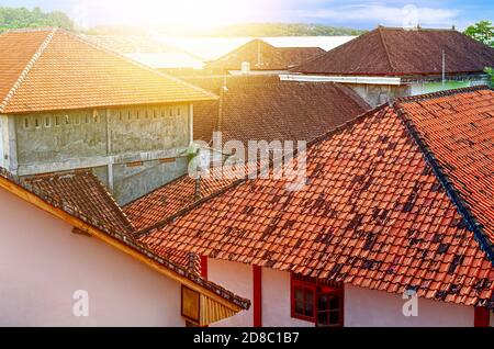 Sunlight from dawn over old houses with tiled roofs. Morning in a small quiet suburb. View from above. City landscape vintage. Asia, Bali. - Stock Photo