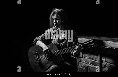 Woman playing guitar, holding an acoustic guitar in his hands. Girl guitarist plays. Girl play the guitar. Woman hipster man sitting in a pub. Black