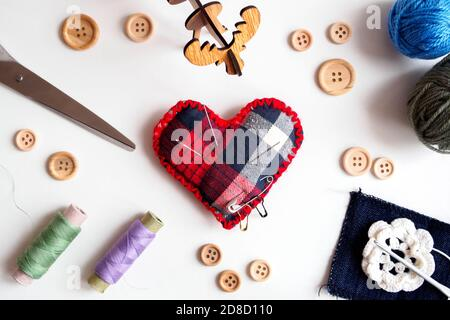 top view of sewing kit with thread, scissors, buttons and needle pillow on white background, flat lay