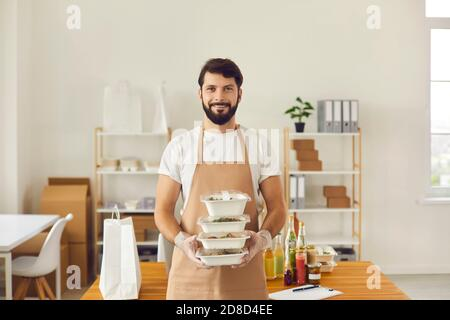 Smiling cafe worker in apron uniform holding ready takeaway lunch orders in food containers - Stock Photo