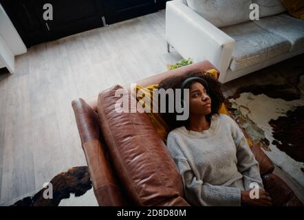 Depressed woman with headphones lying on couch during covid-19 lockdown looking away