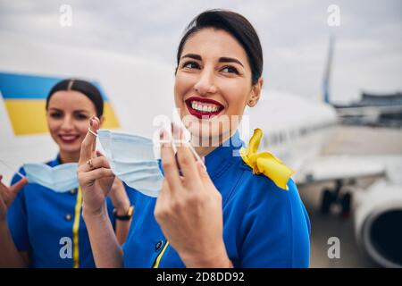 Two stewardesses holding face coverings in their hands - Stock Photo