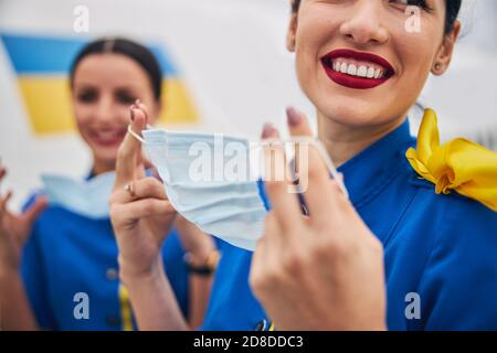 Two young flight attendants putting on face coverings - Stock Photo