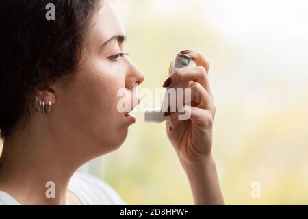 Bronchial asthma. Close-up portrait of a young woman holding an inhaler to her mouth. Side view. - Stock Photo