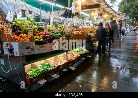 Customers at a fruit stand in the Chelsea neighborhood of New York suffering the remnants of Hurricane Zeta on Thursday, October 29, 2020. Thursday saw steady rain all day continuing into Friday with a drop in temperatures predicted for the weekend. Yikes! (© Richard B. Levine) - Stock Photo