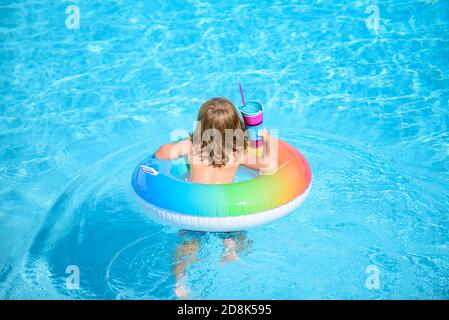 Kid with colorful swim ring in swimming pool on summer day. Water toys and floats for child. Healthy sport for children. Family beach vacation. - Stock Photo