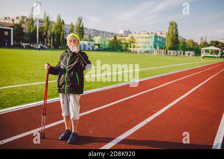 Age maturity, active lifestyle and wellness. Joyful retired woman with walking poles and bottle of water, refreshing during physical activity. Elderly