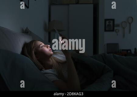 Sleepy exhausted woman lying in bed using smartphone at late night, can not sleep. Insomnia, nomophobia, sleep disorder concept. Addiction on social n