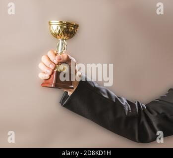The businessman holds the champion's gold trophy, the concept of success and victory