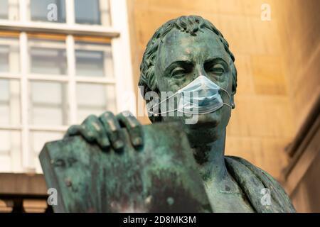Statue of David Hume philosopher wearing facemask  on Royal Mile in Edinburgh, Scotland, UK - Stock Photo