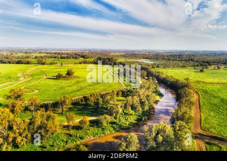 Macquarie river flowing trough Dubbo city in Australian Great Western plains - aerial view in bright sun light over irrigated agriculture farms.