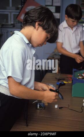 juvenile boys in technology class experimenting with electronics