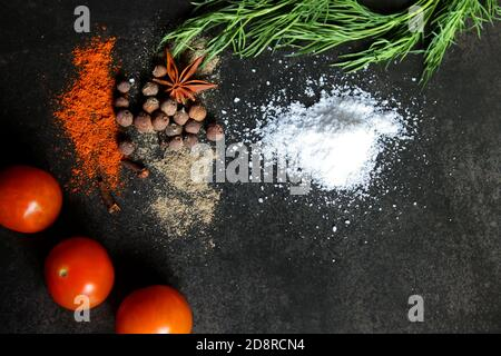 Different kind of spices, dill, parsley, cherry tomatoes on a black stone background. Cafe concept. Delicious food delivery