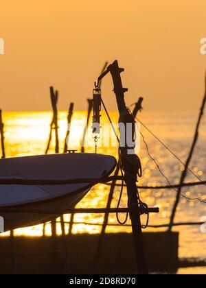 Intensive vivid sunset setting sun Yellow featuring hanging silhouette boat om wooden posts Basanija near Savudrija, Istria Coast in Croatia Europe - Stock Photo