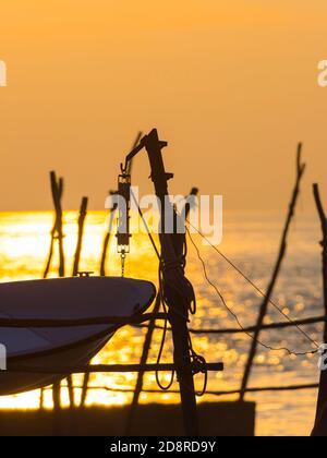Intensive vivid sunset setting sun Yellow featuring hanging silhouette boat bow wooden post Basanija near Savudrija, Istria Coast in Croatia Europe - Stock Photo