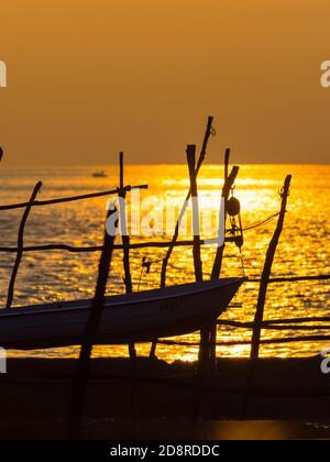 Intensive vivid sunset setting sun Yellow featuring hanging silhouette boat o wooden posts Basanija near Savudrija, Istria Coast in Croatia Europe - Stock Photo