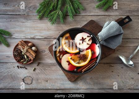Christmas mulled red wine with spices, apples and oranges on  wooden rustic table. Traditional hot drink for Christmas and winter holidays.