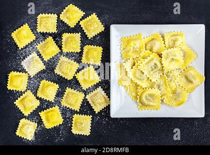 Ravioli with flour and basil on black  background. Italian ravioli making process. Top view - Stock Photo