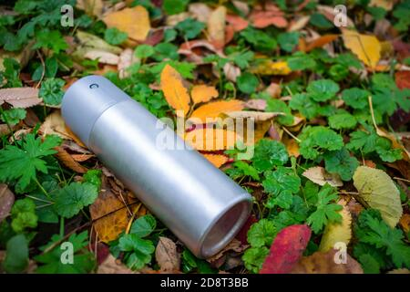 Trash in the form of an antiperspirant spray thrown on the lawn in the autumn foliage