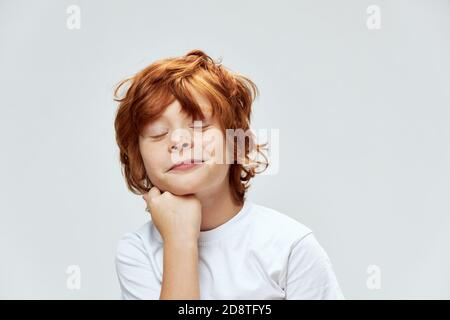 red-haired child with closed eyes holds hand on chin cropped view smile