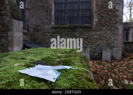 Shallow focus of an incorrectly disposed of Covid-19 face mask seen discarded on a tomb within an English cemetery. - Stock Photo