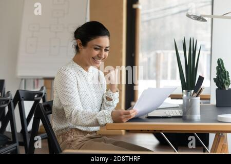 Happy millennial indian woman reading paper letter with good news.