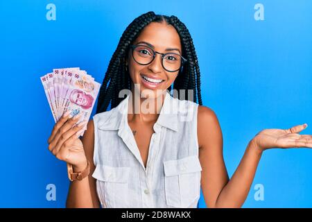 Beautiful hispanic woman holding 50 mexican pesos banknotes celebrating achievement with happy smile and winner expression with raised hand