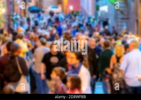 A blur of a crowd of people at dusk. People are gathered on a street between buildings. People are blurred enough not to be recognizable. - Stock Photo