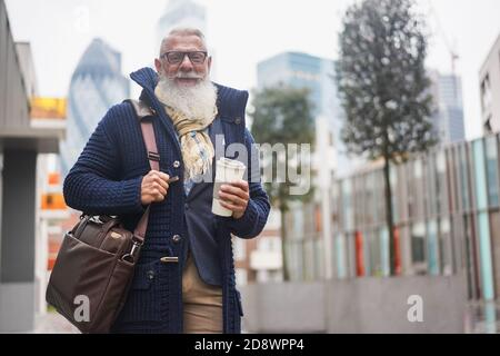 Senior hipster businessman drinking coffee in the city on winter day - Focus on face