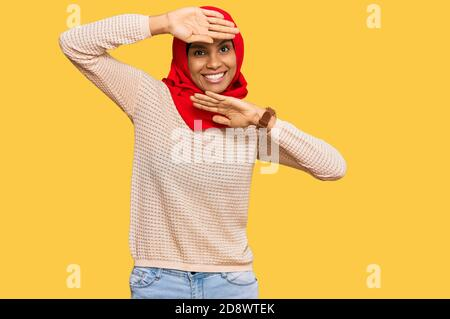 Young african american woman wearing traditional islamic hijab scarf smiling cheerful playing peek a boo with hands showing face. surprised and exited - Stock Photo