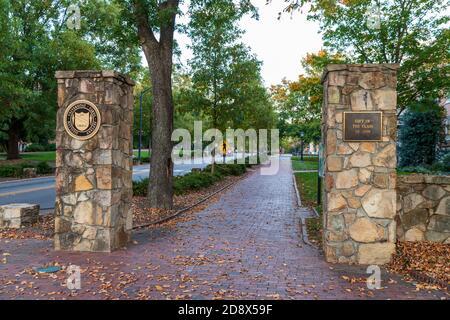 Chapel Hill, NC / USA - October 23, 2020: Stone entrance to the University of North Carolina Chapel hill with brick sidewalk - Stock Photo