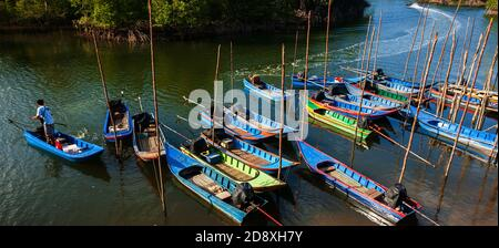 Colourful traditional Asian wooden boats at a local port in a mangrove forest. Ranong, Thailand. High angle view. Panorama view.