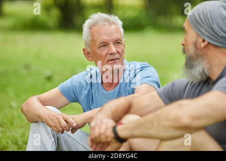 Medium portrait of two modern senior men wearing casual outfits sitting on grass in park discussing something