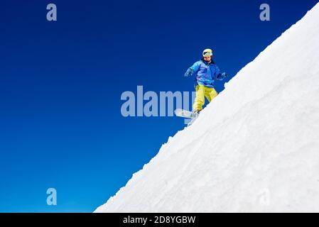 Active man snowboarder riding on white slope inhigh mountains at sunny day against blue sky. Ski season and winter sports concept - Stock Photo