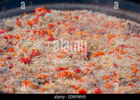 Process of cooking paella shrimp, mussel, rice, tomato, pepper, spice in huge paella pan at summer outdoor food market: close up. Spanish cuisine - Stock Photo