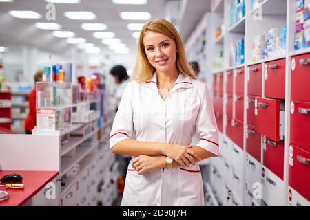 portrait of attractive druggist woman near shelves with medications , posing at camera. smile, wearing white medical uniform
