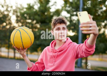 young caucasian basketballer take photo of himself with ball, athletic boy look at smartphone, posing