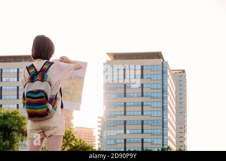 rear view of a young tourist woman with backpack looking a map in front of the city, concept of youth and traveler lifestyle, copy space for text
