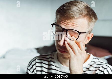 Young businessman feeling sore and tired. Frustrated millennial covering his face with hands . Upset Worker in eyeglasses overworking exhausted. troub - Stock Photo
