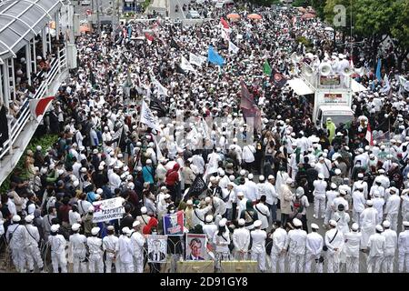 Jakarta, Indonesia. 02nd Nov, 2020. Protesters are seen holding, banners, placards and flags during a protest against French President Emmanuel Macron in Jakarta.Indonesian Muslims marched to a heavily guarded French Embassy in Indonesia's capital on Monday to protest against French President and his staunch support of secular laws that deem caricatures depicting the Prophet Muhammad as protected speech. Credit: SOPA Images Limited/Alamy Live News - Stock Photo