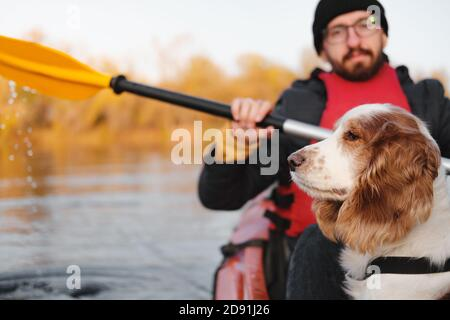 Man rowing a canoe with his spaniel dog, sunny autumn weather. Going kayak boating with dogs on the river, active pets, happy dog and owner on an adve Stock Photo