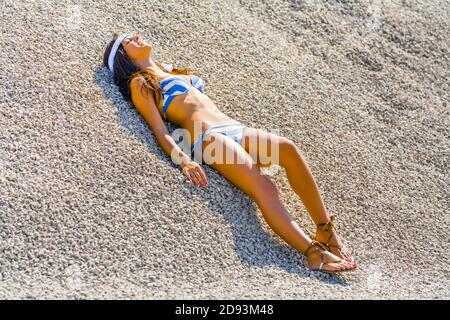 Teengirl wearing Blue-White bikini swimsuit in nature lying on back on beach sand dune bright sunlight sunshine sunny leisure pose - Stock Photo