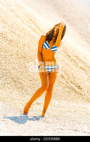Teengirl wearing Blue-White bikini swimsuit in nature standing sunbathed sunlit hand cover protect head eyes on beach sand dune messy untidy hair - Stock Photo